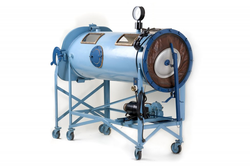 Iron lung with large light blue cylinder to fit an adult, mounted about three feet high on casters, a portal for head on one end and bellows on the other, electrical motor on base, weighing 750 pounds, 1931