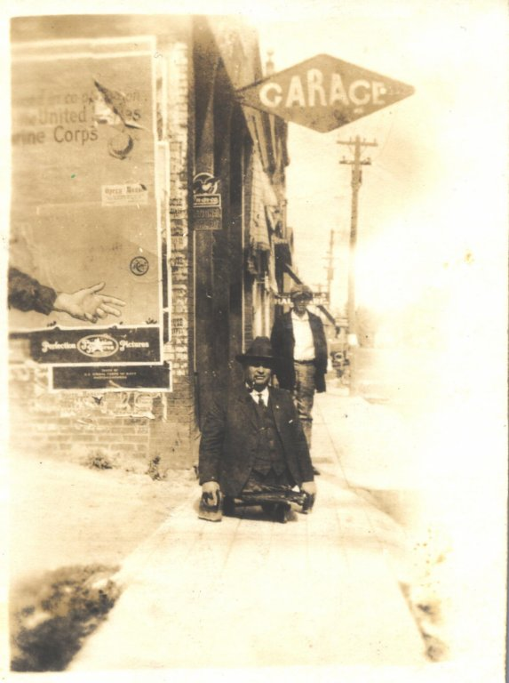 adult male on knuckle board in city sepia photograph disability history america