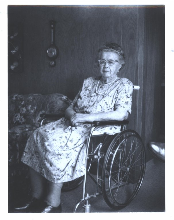 An elderly woman sitting at home in her wheelchair
