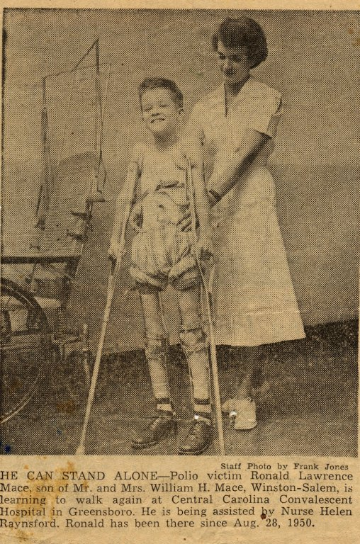 little boy held by female nurse and crutches black white photograph disability history america
