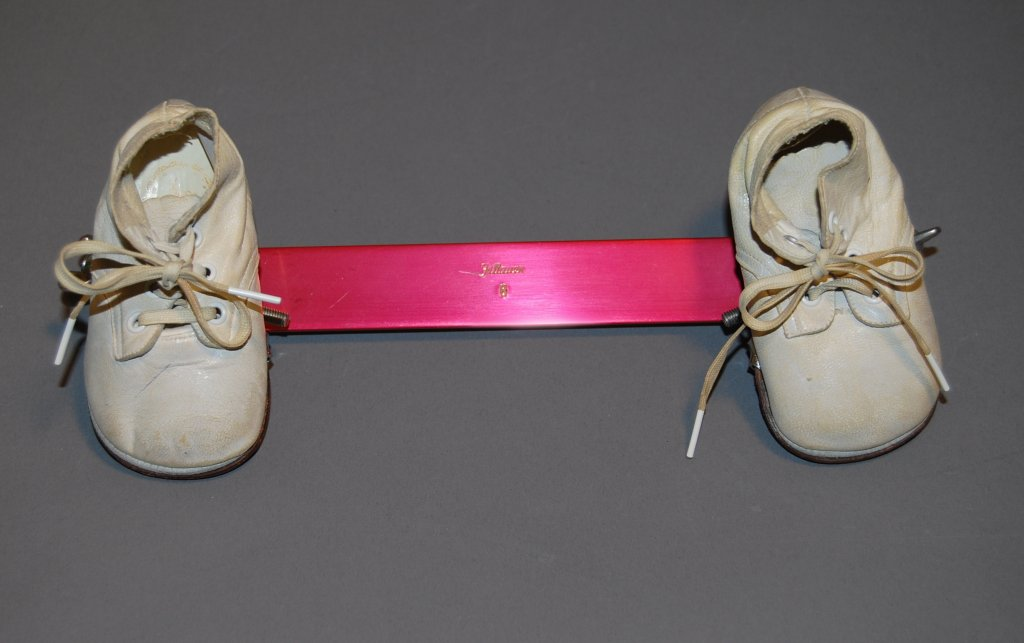pair of shoes connected by pink device disability history america