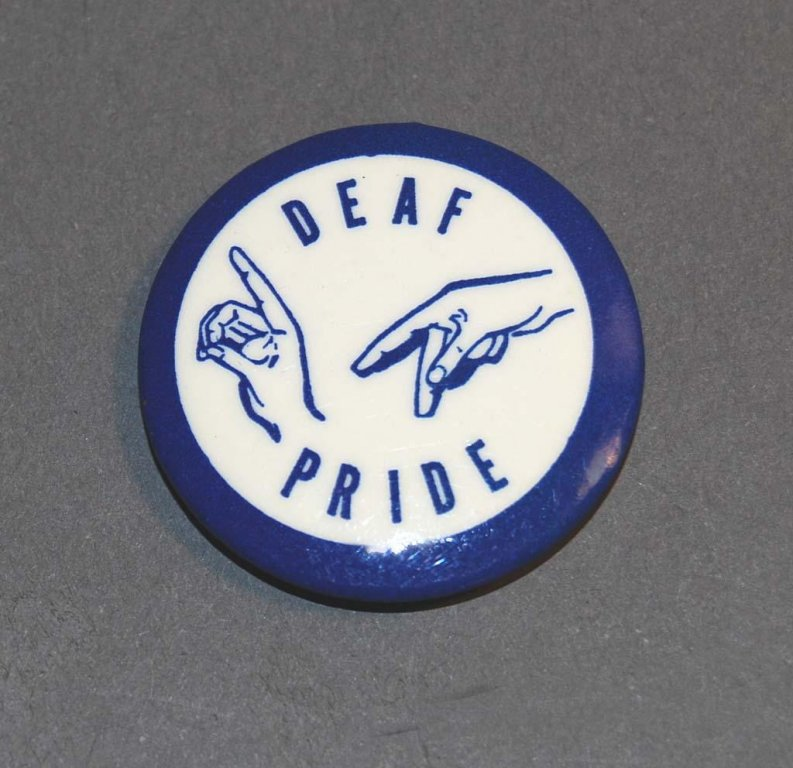 "Button showing two hands signing D and P, and the words ""Deaf Pride,"""