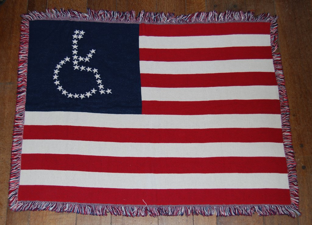 A woven American flag lap blanket, featuring stars in the shape of the universal access symbol.