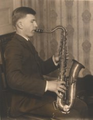 seated adult male saxophonist sepia photograph disability history america