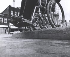 wheelchair at curb without ramp black white photograph disability america
