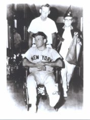 Photo of Mickey Mantle with a broken foot being pushed in a wheelchair