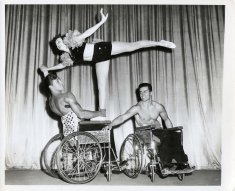 Two muscular men in wheelchairs balance a woman in an arabesque pose.