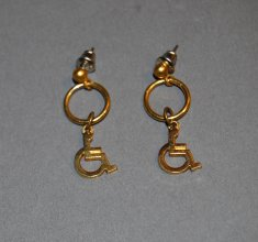 A pair of gold earrings feature the shape of the universal access symbol.