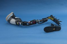 An artificial leg fitted with a claw-cleat attachment, and a boot-tread attachment lying beside.