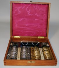 A red silk lined wooden box containing several dozen lenses for testing vision